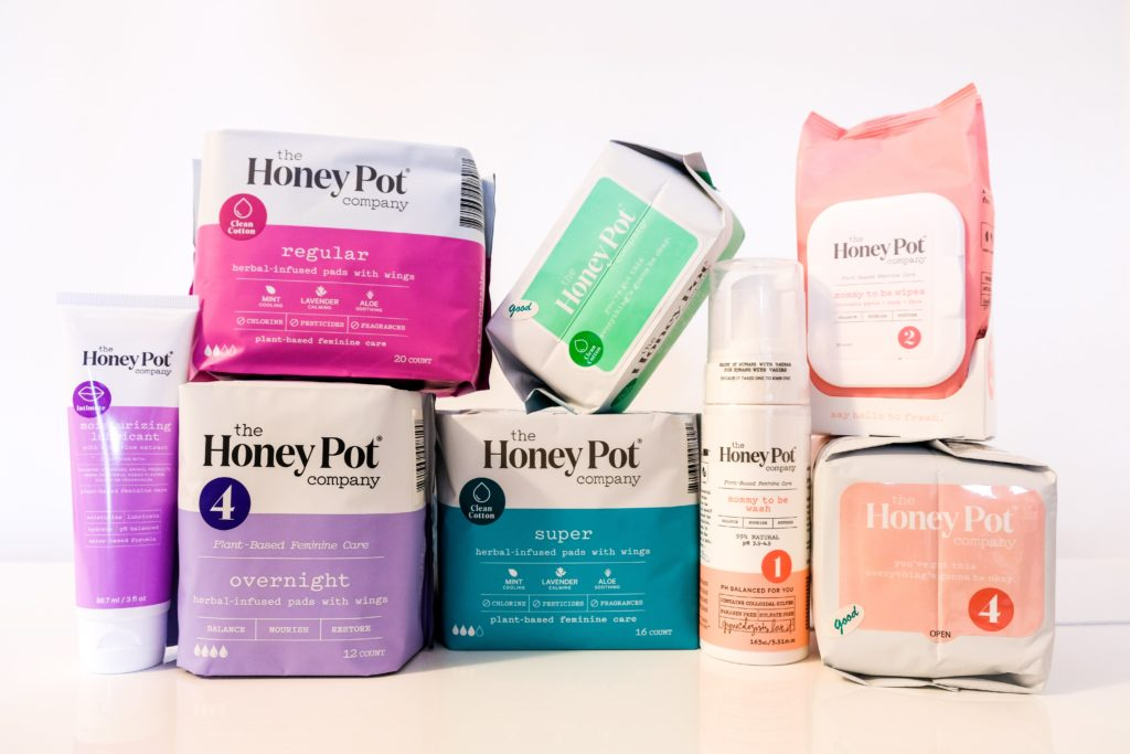 Array of The Honey Pot Co plant-based products including mommy-to-be, pads and moisturizing lubrication